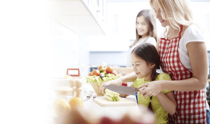 Family smiling, cutting vegetables and cooking together