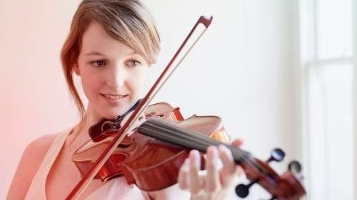 Woman smiling, playing the violin